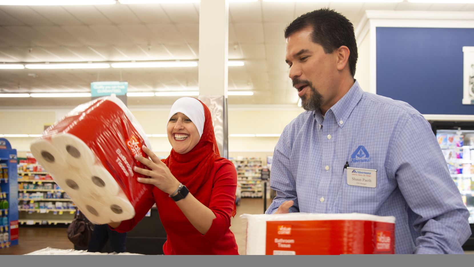 Maha Eldabaja, Center Store Operations Specialist, (left) and Shaun Paeth, head of general merchandise, refill the toilet paper spillover display at Albertsons last week in Colleyville.