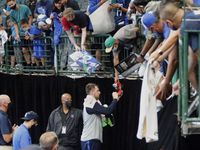 Dallas Mavericks guard Luka Doncic (77) autographs a shoe for one of the fans after the event as the Dallas Mavericks held their Mavs Fam Jam, a scrimmage free to the public at the American Airlines Center in Dallas on Sunday, October 3, 2021.