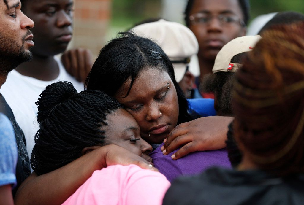 Tina Tyler, the mother of Malik Tyler, gets hugs from friends and family during a vigil for Malik near the scene of the shooting in Dallas on Wednesday, June 5, 2019. Tyler was injured and killed in crossfire in the 9400 block of Bruton Road Tuesday night. (Vernon Bryant/The Dallas Morning News)