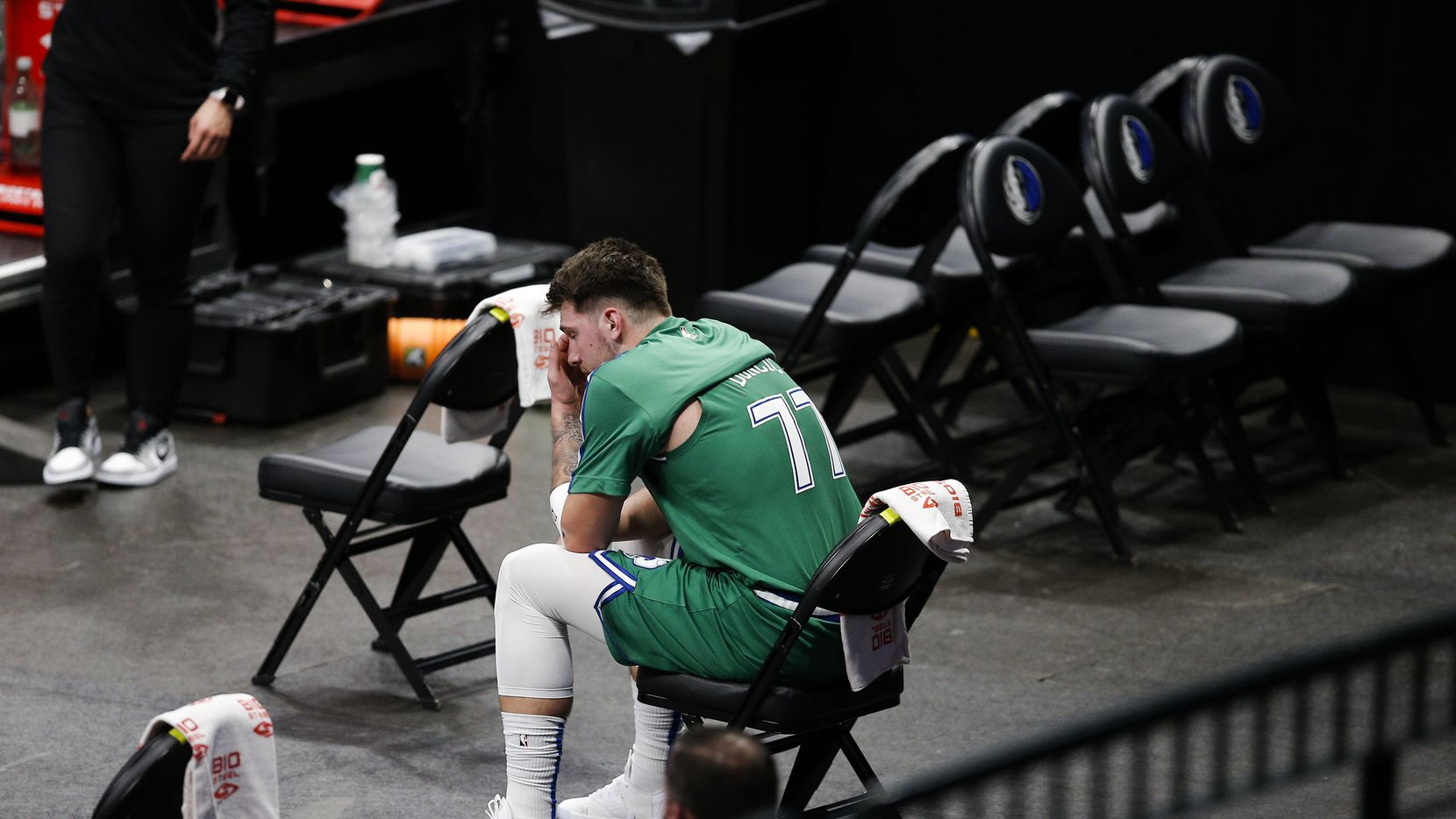 Dallas Mavericks guard Luka Doncic (77) looks on from the bench after committing a technical foul during the first half of an NBA basketball game against the Phoenix Suns in Dallas, Saturday, January 30, 2021.