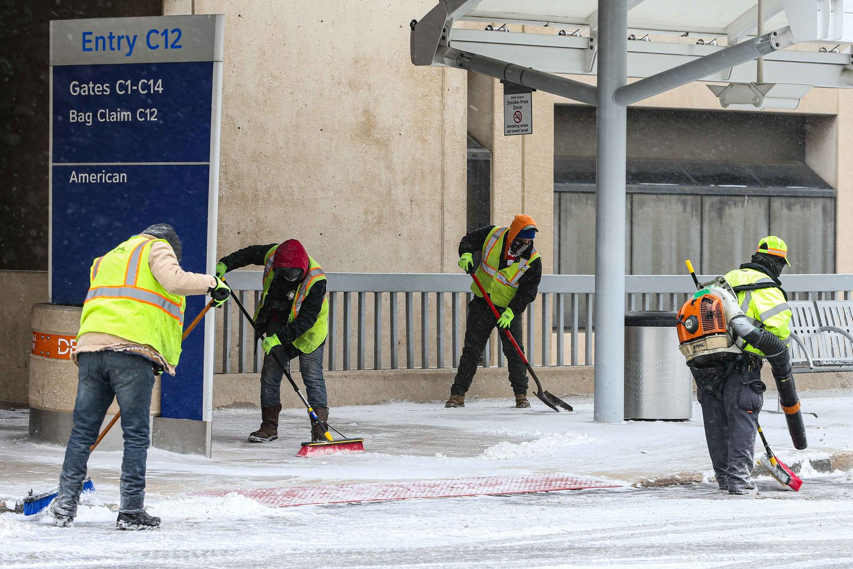 Workers keep the sidewalks clear as snow, ice decend over DFW International Airport. American cancel hundreds of flights in Irving on Sunday, February 14, 2021.
