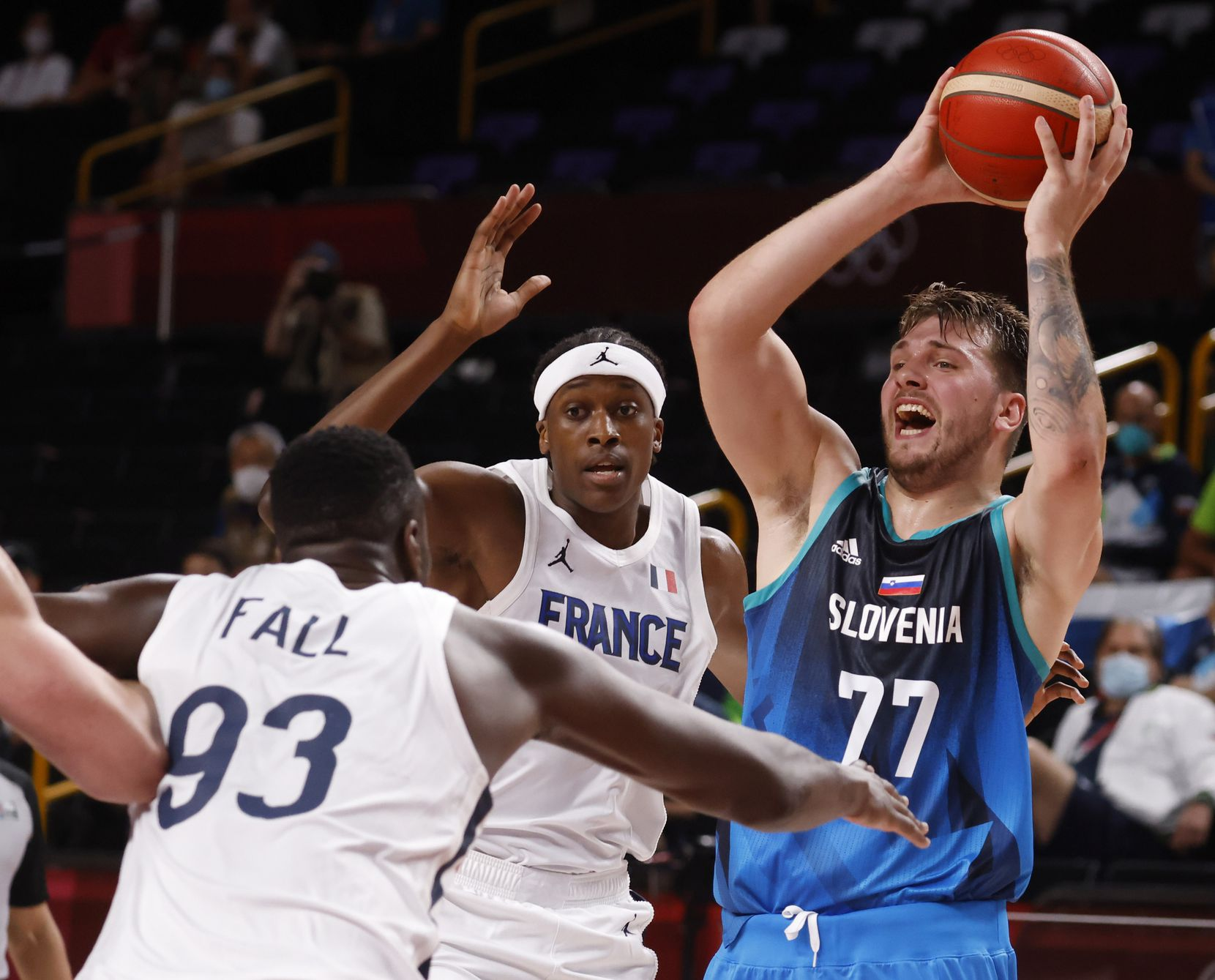 Slovenia's Luka Doncic (77) looks to pass as France's Moustapha Fall (93) steps up to defend during the first half of a men's basketball semifinal at the postponed 2020 Tokyo Olympics at Saitama Super Arena, on Thursday, August 5, 2021, in Saitama, Japan. (Vernon Bryant/The Dallas Morning News)