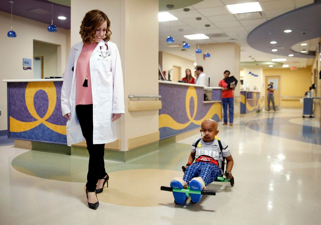 Dr. Tiffany Simms-Waldrip (left) walks the halls of the Stem Cell Transplant Unit with patient Akshaj Nagilla, who uses an exercise roller, at Children's Medical Center Dallas on Jan. 15, 2019. Akshaj, 7, just received a second transplant to treat his leukemia. Simms-Waldrip is a associate professor of pediatrics at UT Southwestern Medical Center and clinical director of the marrow transplant program at Children's Health.
