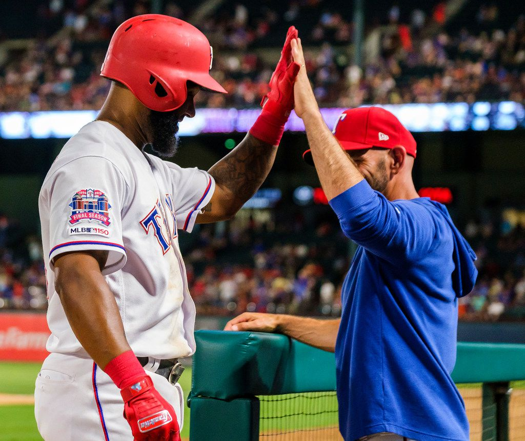 Texas Rangers first baseman Danny Santana (38) gets a hand from manager Chris Woodward after hitting al home run during the sixth inning against the Seattle Mariners at Globe Life Park on Tuesday, July 30, 2019, in Arlington. (Smiley N. Pool/The Dallas Morning News)
