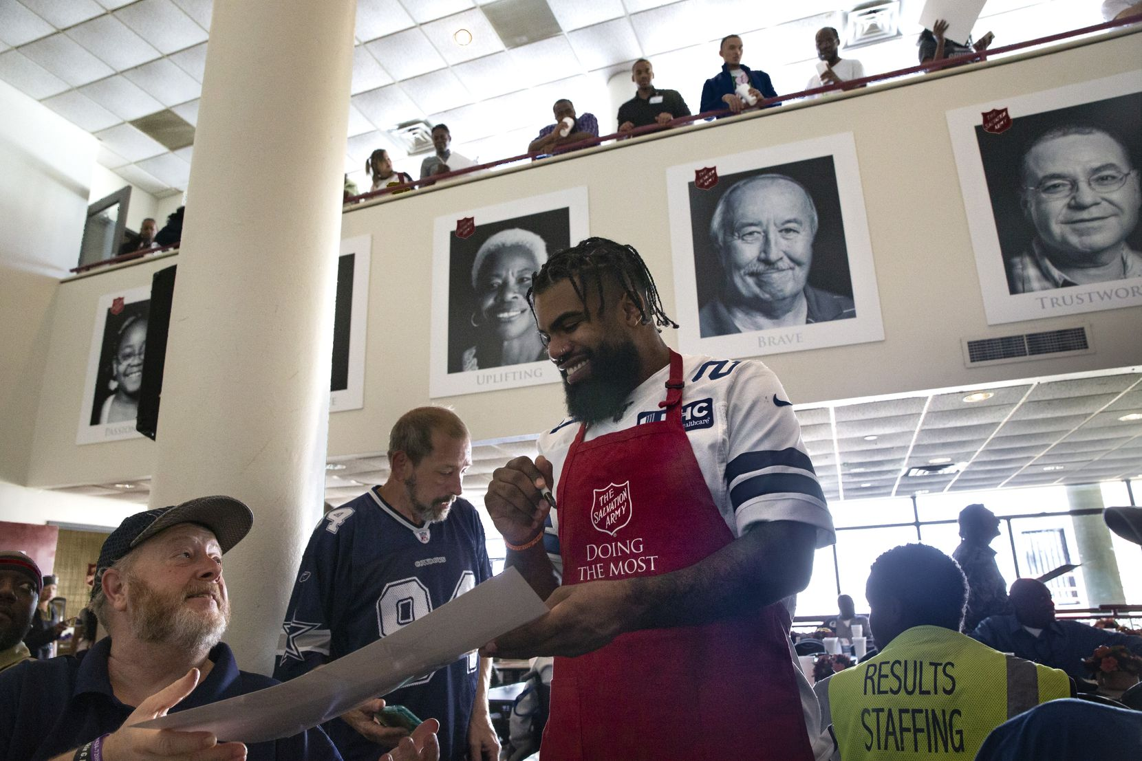 Dallas Cowboys running back Ezekiel Elliott (center) signs autographs after Elliott and other Dallas Cowboys helped serve an early Thanksgiving lunch to clients at The Salvation Army Carr P. Collins Social Service Center in Dallas on Tuesday, November 19, 2019.