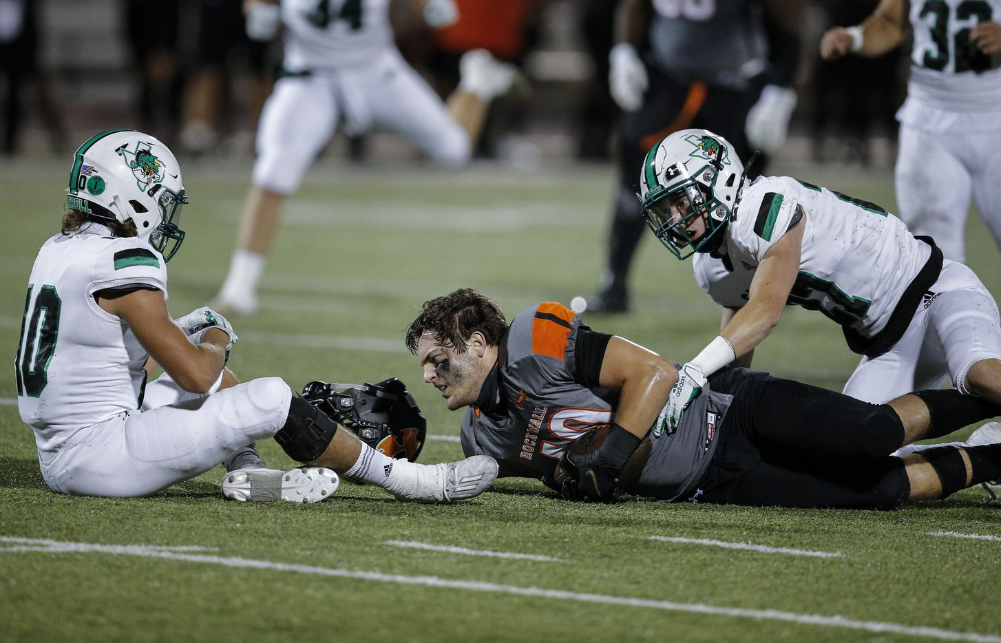 Southlake Carroll sophomore defensive back Jon Cox (10) and senior defensive back Mason Grawe (27) tackle Rockwall junior tight end Brenna Ray (40) during the first half of a high school football game at Wilkerson-Sanders Stadium in Rockwall, Thursday, October 8, 2020. (Brandon Wade/Special Contributor)