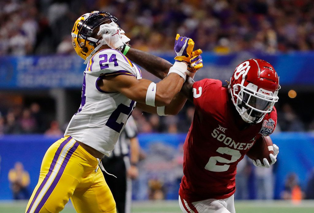 ATLANTA, GEORGIA - DECEMBER 28: Wide receiver CeeDee Lamb #2 of the Oklahoma Sooners carries the ball against Chris Curry #24 of the LSU Tigers during the Chick-fil-A Peach Bowl at Mercedes-Benz Stadium on December 28, 2019 in Atlanta, Georgia. (Photo by Kevin C. Cox/Getty Images)