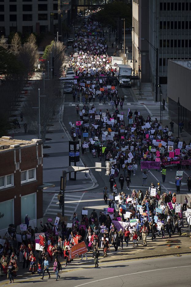 Participants in the 2020 Dallas Women's March walk along Harwood Street on their way to a rally at Dallas City Hall on Sunday, Jan. 19, 2020, in Dallas.