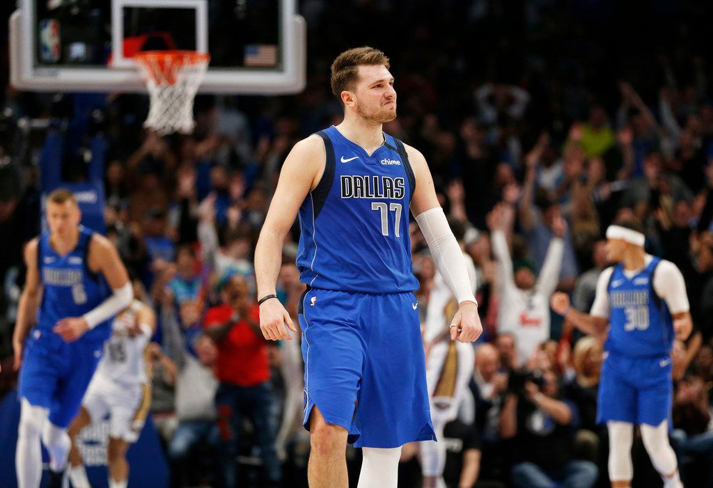 FILE - Mavericks guard Luka Doncic (77) smiles after making a 3-pointer late in overtime play over Pelicans center Derrick Favors (22) at American Airlines Center in Dallas on Wednesday, March 4, 2020.