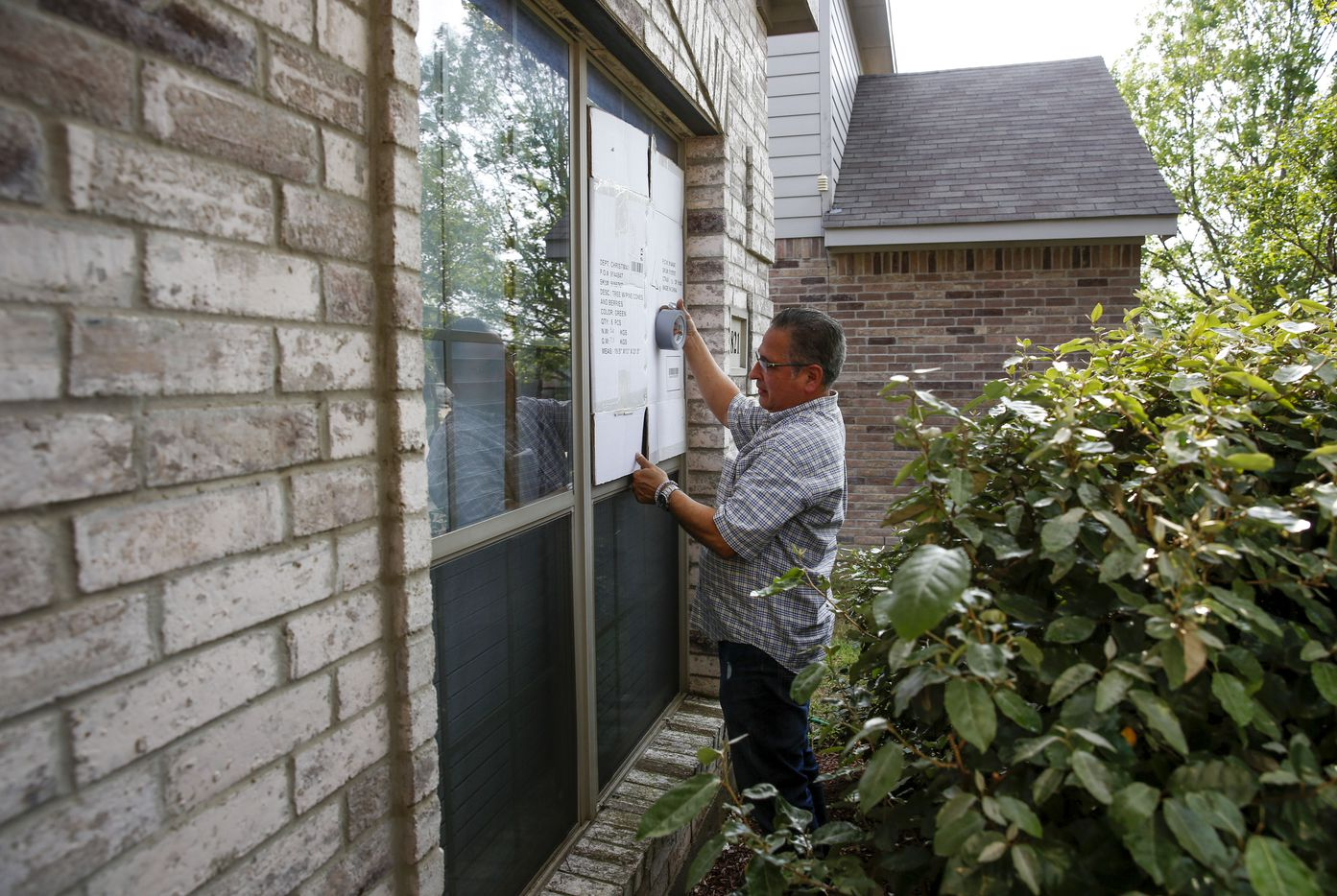 Michael Ruiz of McKinney tapes boxes to the front windows of his house to protect them from hail damage as the threat of storms get closer on April 17, 2019 in McKinney, Texas (Brian Elledge/The Dallas Morning N