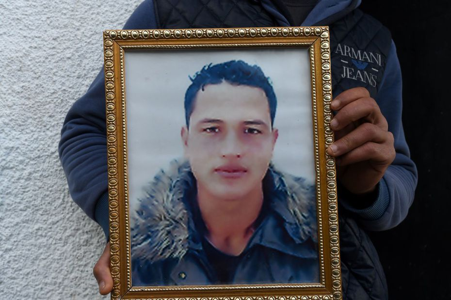 This file photo taken on December 23, 2016 shows Walid Amri (back), the brother of 24-year-old Anis Amri, the suspected Berlin truck attacker, posing with a portrait of his brother Anis in front of the family house in the town of Oueslatia, in Tunisia's region of Kairouan.