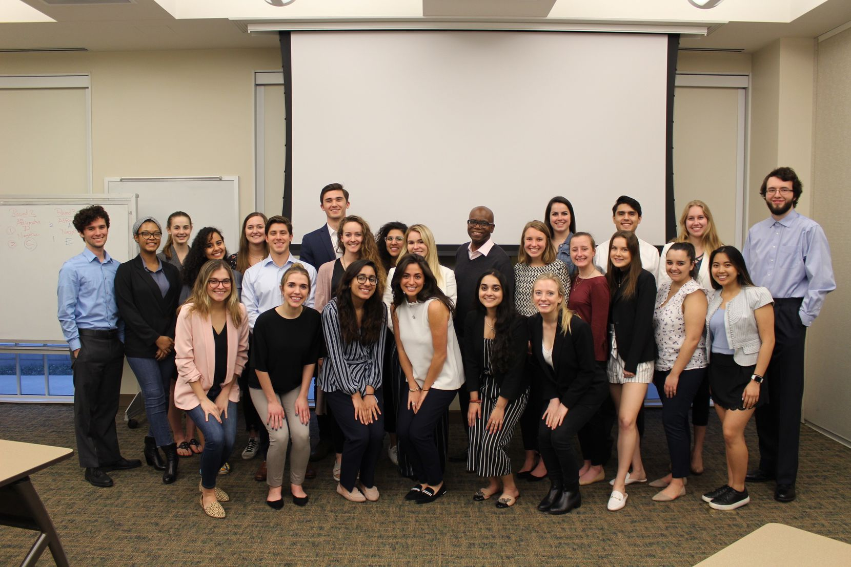 "Dr. Eric Bing (back center) poses with the students in his 2020 ""Creating Global and Public Health Impact"" course before the pandemic at SMU in Dallas, Texas. Khris Beeson (front right) took Bing's class on the advice of a friend."