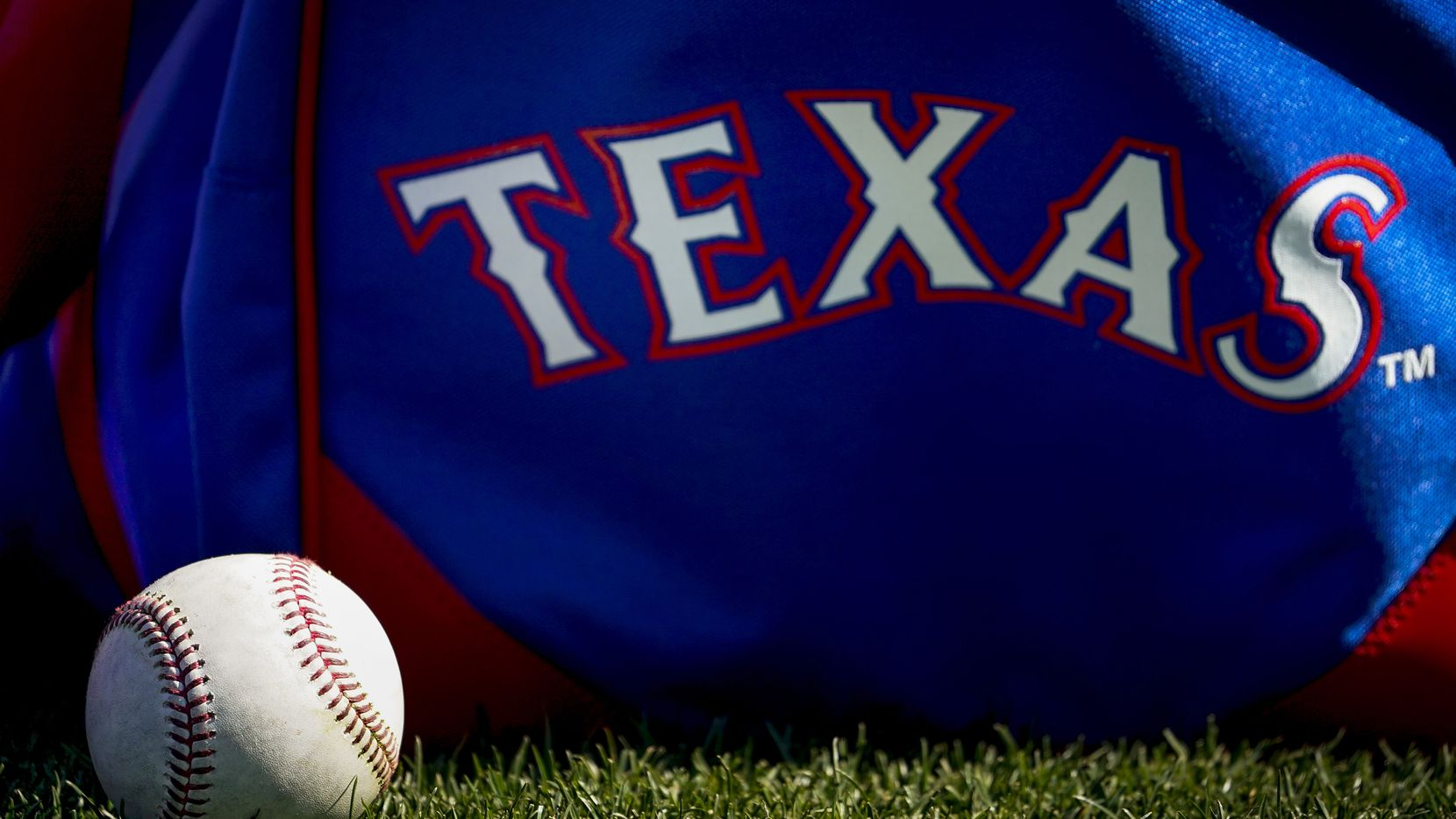 A baseball rests next to a Rangers player's bag during a spring training workout at the team's training facility on Thursday, Feb. 20, 2020, in Surprise, Ariz.