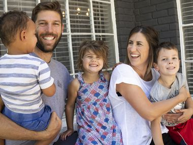 Ryan and Taylor Hollingshead, center right, and their children Huck, right, 4, Quinn, center, 3, and a 2-year-old foster baby pose for a portrait at their home in Richardson on Thursday, May 6, 2021. Ryan and Taylor have been active foster parents for a few years, and they're in the process of finalizing the adoption process on their current foster child, who just turned two. The family requested his face and name not be used before the adoption process is finalized.