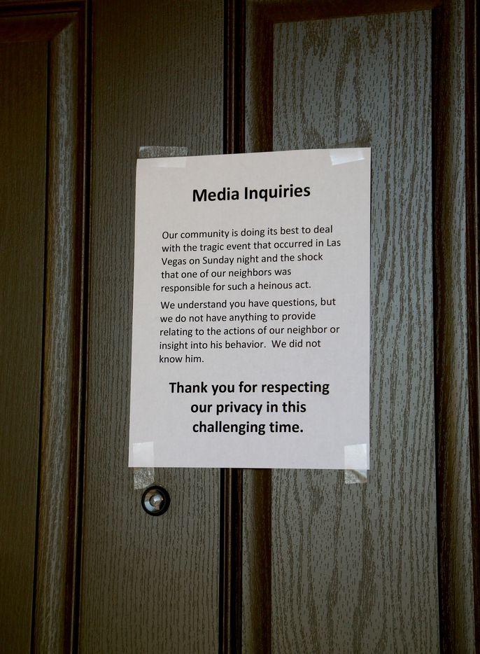 A sign posted on a neighbor's door next to the house where suspected Las Vegas gunman Stephen Paddock lived on October 2, 2017 in Mesquite, Nevada.