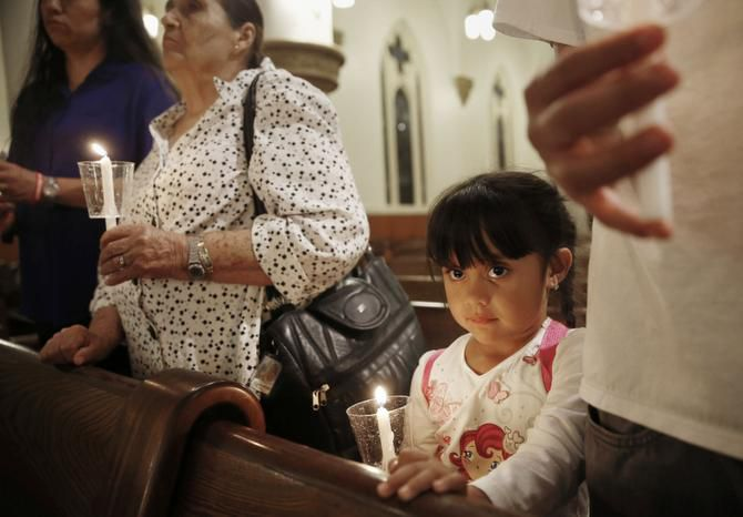 Evelin Garcia, 4, along with (from left) her mother, Esthela Estrada; her grandmother, Josofen Alvers; and her brother, Efren Garcia, prayed for Ebola patients and caregivers at The Cathedral Shrine of the Virgin of Guadalupe in Dallas on Thursday.