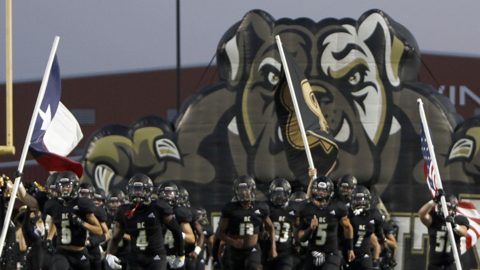 Members of the Royse City Bulldogs storm the field as they emerge from their team inflatable mascot prior to the opening kickoff of their game against Frisco Centennial. The two teams played their Class 5A football game at Royse City ISD Stadium in Royse City on September 25, 2020.