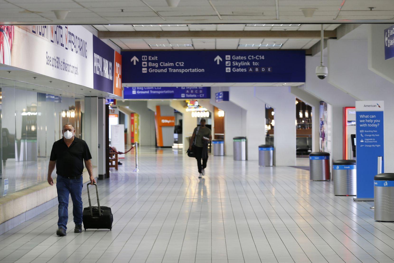 People make their way through terminal C at DFW International Airport on Wednesday, April 8, 2020.