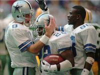 Dallas Cowboys Troy Aikman (8), Emmitt Smith (22) and Michael Irvin (88) celebrate Smith's second-quarter touchdown run in the NFC Championship game against the Green Bay Packers in Irving, Texas, in this January 14, 1996 photo.