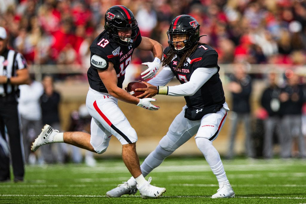 Quarterback Jett Duffey #7 of the Texas Tech Red Raiders fakes a handoff to McLane Mannix #13 during the first half of the college football game against the TCU Horned Frogs on November 16, 2019 at Jones AT&T Stadium in Lubbock, Texas.