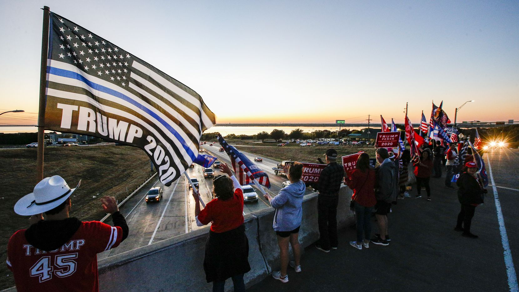 Members of the Trump Train 2020 DFW group wave flags and signs in support of Pres. Donald Trump on Horizon Road over looking I-30 in Rockwall, Monday, November 2, 2020.