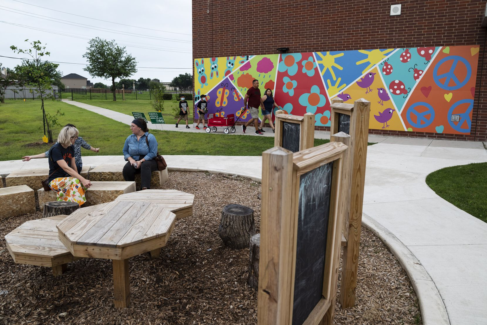 Families and parks advocates gathered Tuesday evening to celebrate the opening of the new and expanded greenspace for the community at Frank Guzick Elementary in the Buckner Terrace neighborhood south of Interstate 30. Artist Abi Salami created the mural for this Cool School Neighborhood Parks location.