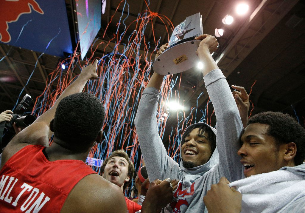 Ben Moore hoists the trophy as Southern Methodist Mustangs celebrate winning the American Athletic Conference regular season conference title at Moody Coliseum in Dallas on March 4, 2017 by beating Memphis by a score of 103-62. (Nathan Hunsinger/The Dallas Morning News)