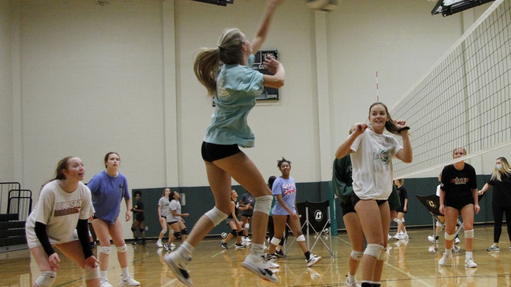 Grayson Reed skies to fire a shot as she is flanked by teammates Tatum Pavey, left, and Bryley Steinhilber, right, during a practice session for the Kennedale Lady Kats volleyball team. Under the direction of head coach Kelly Carl, the team conducted their first practice of the season at Kennedale High School in Kennedale on August 03, 2020.(Steve Hamm/ Special Contributor)