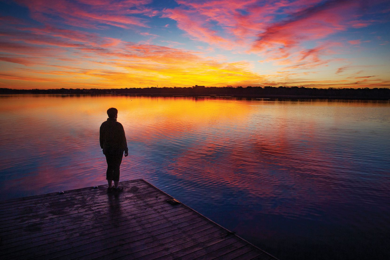 """Amy Hofland, a survivor of thyroid cancer, stands before the sunrise over White Rock Lake in Dallas during the early morning rush hour on Wednesday, March 25, 2020. Hofland has been taking sunrise photos since 2011 as part of her journey to healing from cancer, and she hopes to compile her archive into a book for cancer patients. """"When you're going through cancer, this is what you run towards. Another beginning,"""" Hofland said of Wednesday's sunrise."""