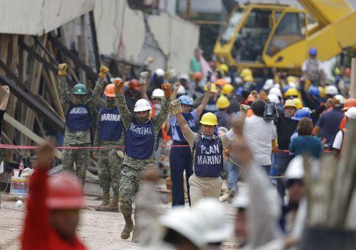 Soldados sostienen los puños cerrados en alto pidiendo silencio durante los esfuerzos de rescate en la escuela Enrique Rébsamen en la Ciudad de México, el jueves 21 de septiembre de 2017. (AP Foto/Rebecca Blackwell)