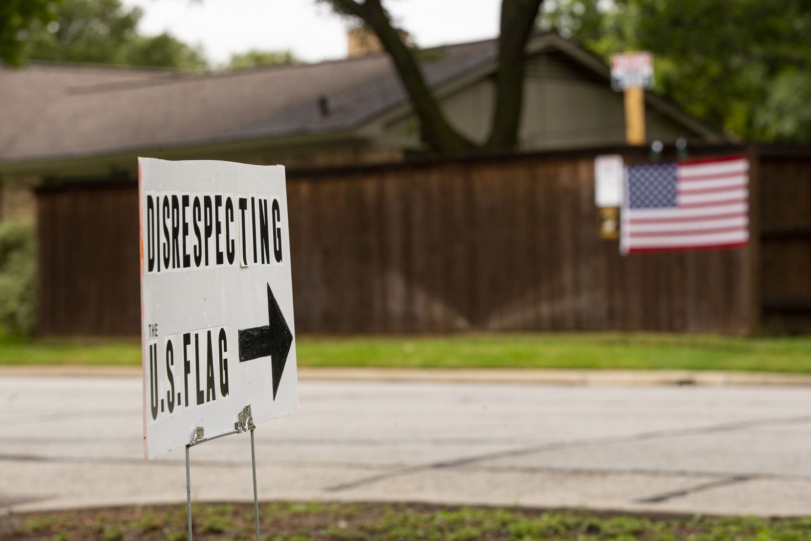 A sign outside of Brenda Drevicky's home points to her neighbor's signs on Sept. 10, 2020 in Farmers Branch. Drevicky put the sign up because she said her neighbor is not following the U.S. flag code. (Juan Figueroa/ The Dallas Morning News)