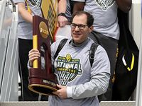 Baylor men's basketball Head Coach Scott Drew carries the NCAA Division I National Championship trophy as he exits the plane Tuesday, April 6, 2021, in Waco, Texas.