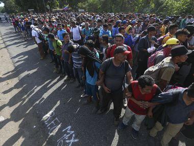 Migrantes forman una cadena sujetándose por los brazos en una carretera hacia Tapachula, México, el 23 de enero de 2020.