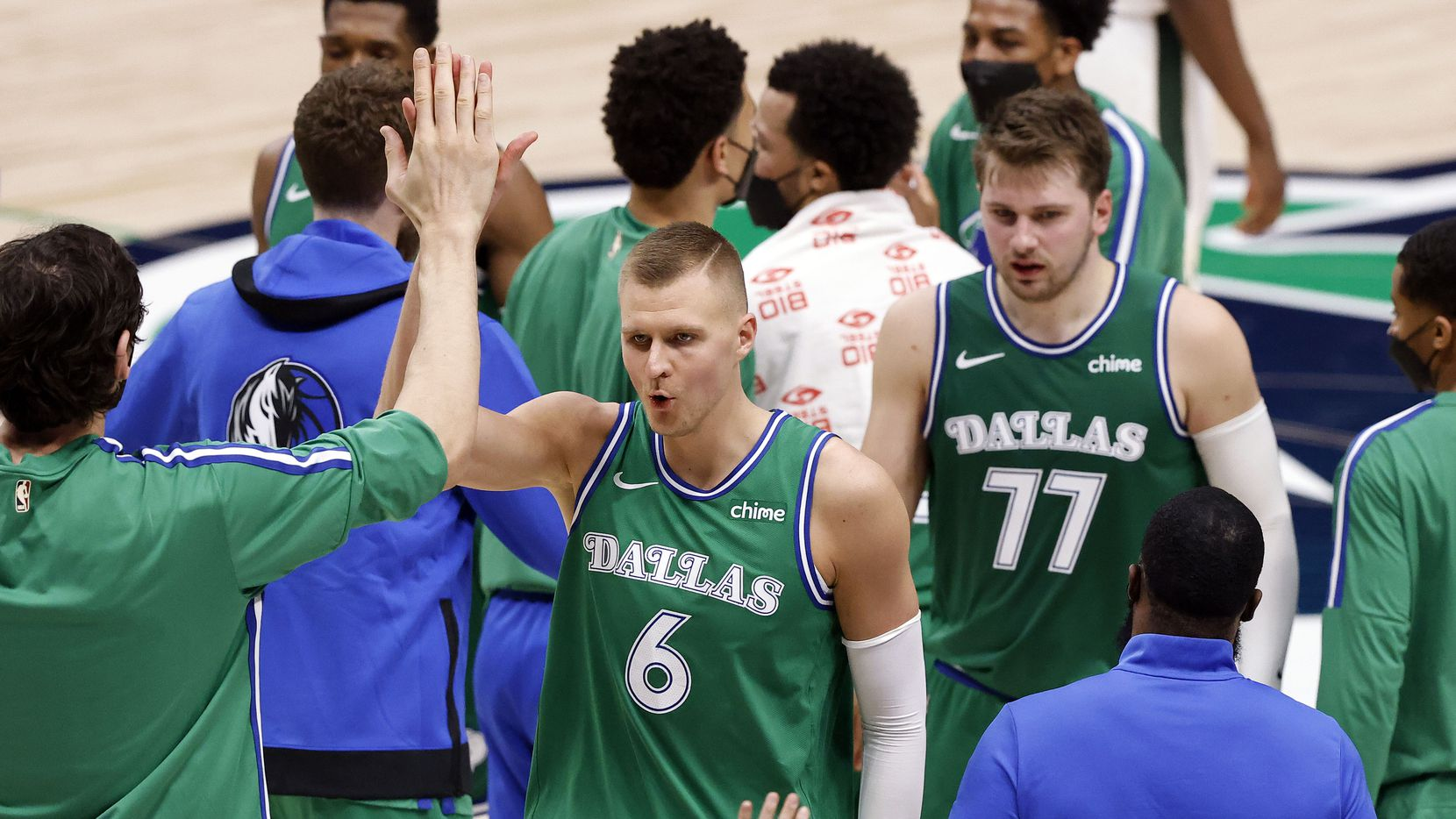 Dallas Mavericks center Kristaps Porzingis (6) is congratulated by teammates for his fourth quarter play against the Milwaukee Bucks at the American Airlines Center in Dallas, Thursday, April 8, 2021. The Maverick defeated the Bucks, 116-101. (Tom Fox/The Dallas Morning News)