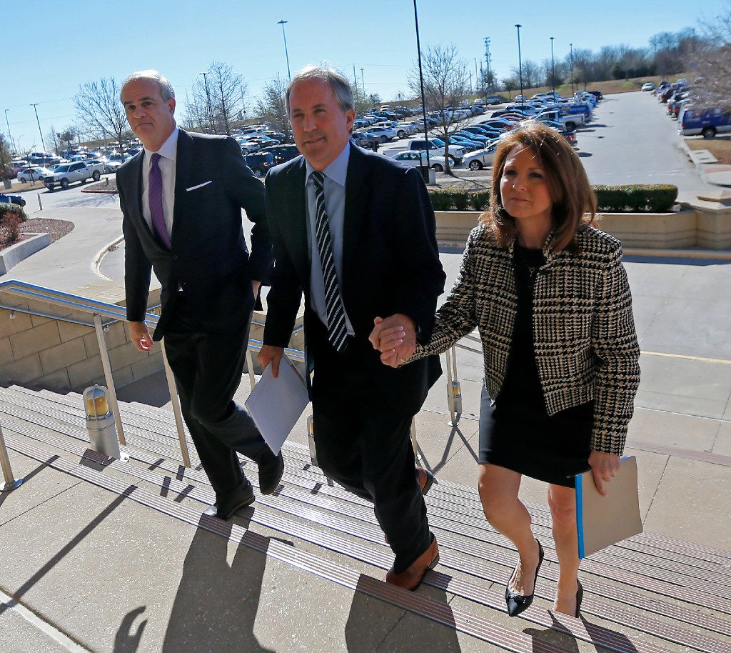 Texas Attorney General Ken Paxton (center) arrives the Collin County Courthouse with his wife, Angela,  and attorney Phillip Hilder for his pretrial hearing in McKinney on Feb. 16.