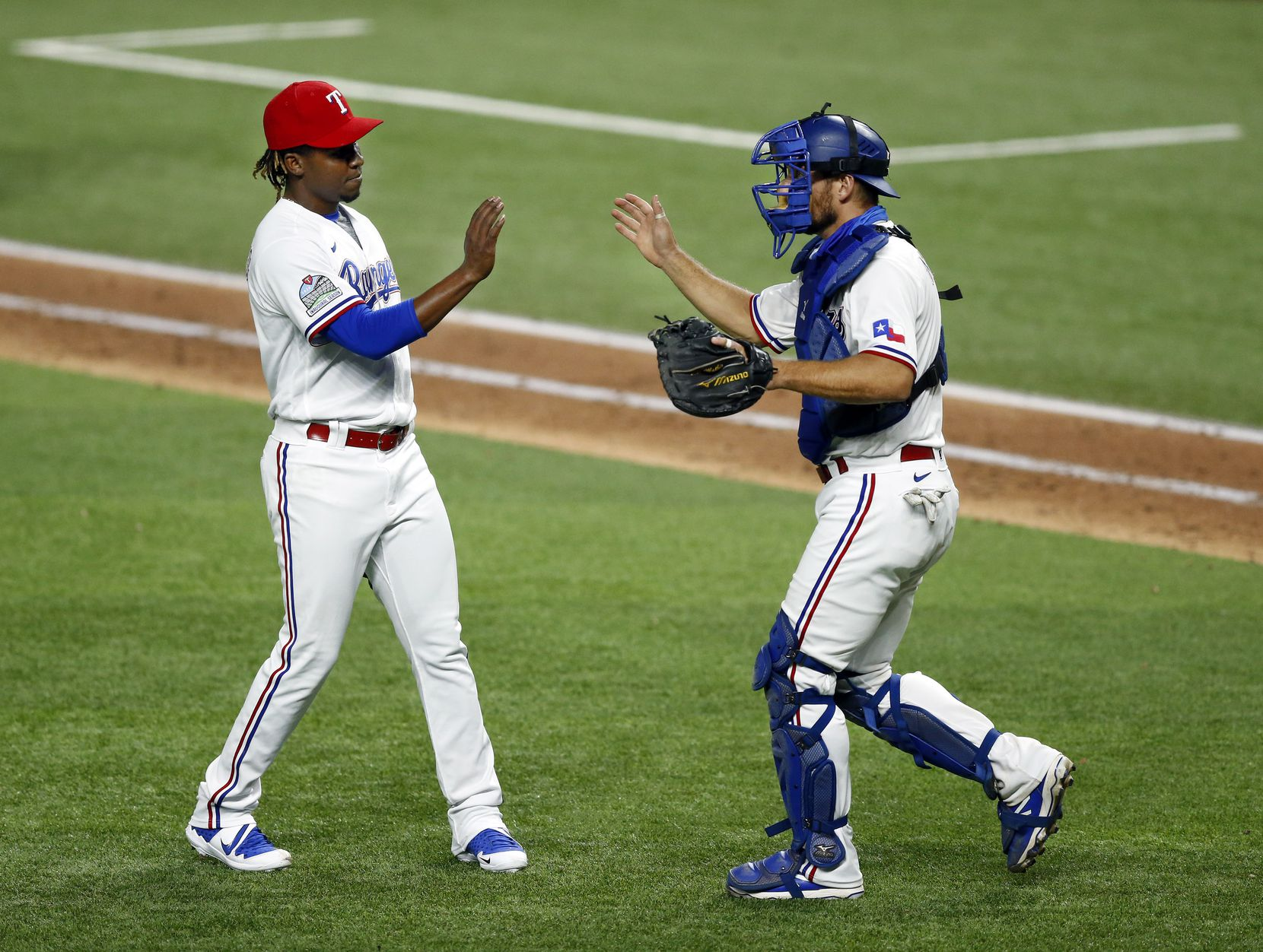 Texas Rangers relief pitcher Rafael Montero (left) is congratulated on his save by catcher Jeff Mathis after defeating the Seattle Mariners, 4-2, at Globe Life Field in Arlington, Tuesday, August 11, 2020. (Tom Fox/The Dallas Morning News)