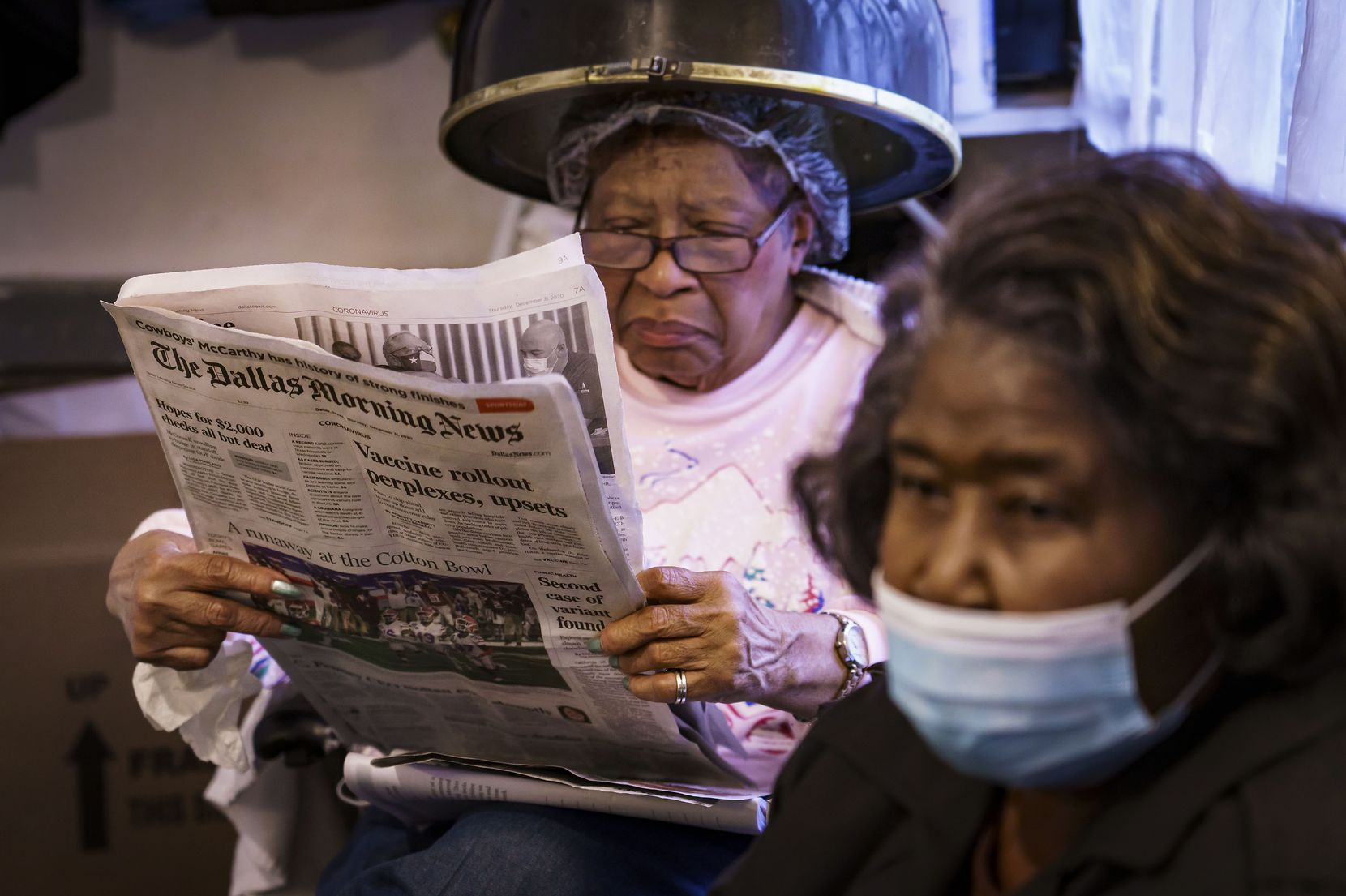 Client Vera Harris reads the newspaper as she sits under a hair dryer at the beauty shop of Earnestine Tarrant in South Dallas on New Year's Eve.