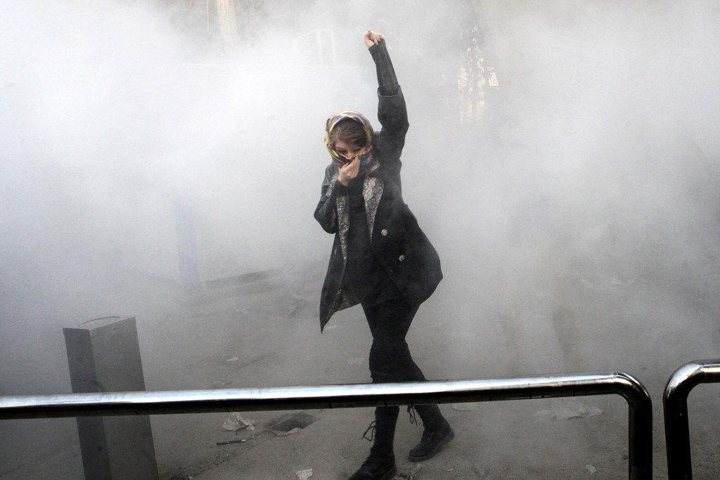 In this Dec. 30, 2017 photo made by an individual not employed by the Associated Press and obtained by the AP outside Iran, a university student attends a protest inside Tehran University while a smoke grenade is thrown by Iranian police, in Tehran, Iran.