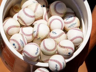Texas Rangers infielder Greg Bird dumps a bucket of baseballs from infield practice into a bag during a spring training workout at the team's training facility on Thursday, Feb. 13, 2020, in Surprise, Ariz.