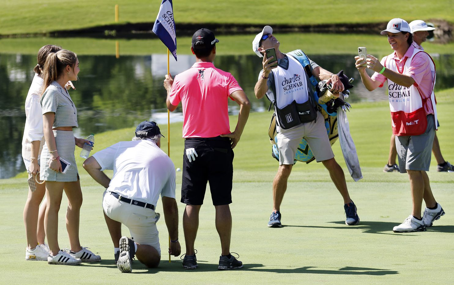 Golfer Kevin Na (pink shirt) poses for photos with playing partner Mitchell Parks (kneeling) after Parks hit a hole-in-one on No. 17 during the Charles Schwab Challenge Colonial Pro-Am at the Colonial Country Club in Fort Worth, Wednesday, May 26, 2021. Na won the tournament in 2019. (Tom Fox/The Dallas Morning News)