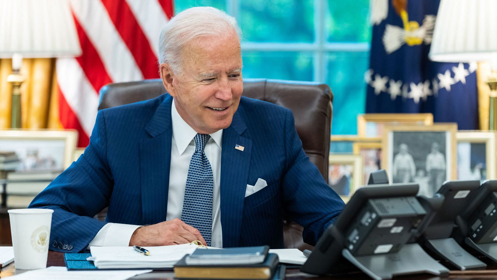 In this image released by the White House, President Joe Biden talks on the phone with French President Emmanuel Macron on Sept. 22, 2021, in the Oval Office, the presidents' first conversation since a row erupted over the sale of submarines to Australia.