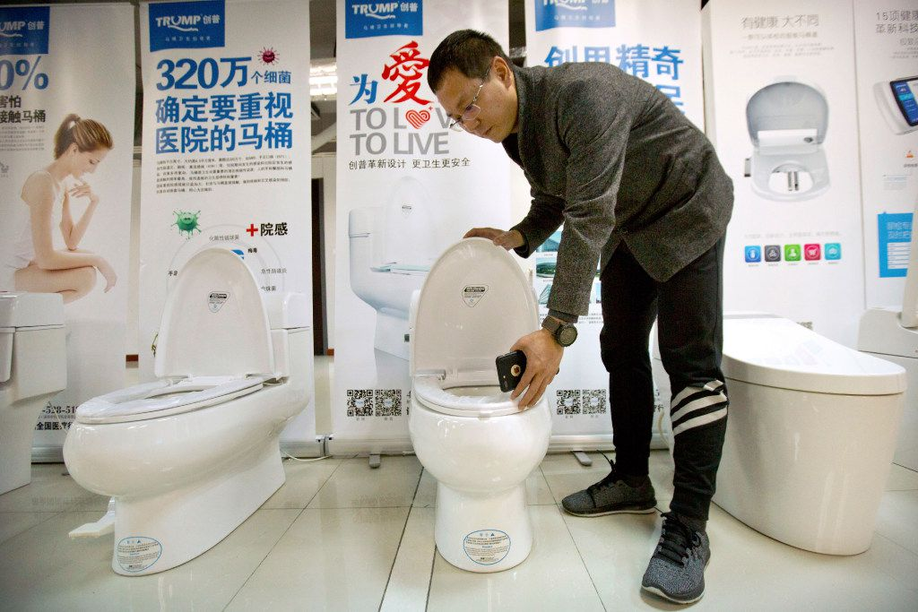 Zhong Jiye, a co-founder of Shenzhen Trump Industrial, shows one of his firm's high-end Trump-branded toilets at the company's offices in Shenzhen in southern China's Guangdong province.  (Mark Schiefelbein/The Associated Press)