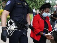 """WASHINGTON, DC - JULY 29: U.S. Rep. Sheila Jackson Lee (D-TX) (R) is arrested by a member of U.S. Capitol Police as she participates in a civil disobedience during a protest outside Hart Senate Office Building on Capitol Hill July 29, 2021 in Washington, DC. Black women voting rights leaders and allies took part in a """"Day of Action on Capitol Hill"""" event calling on the U.S. Senate to pass the For the People Act and end the filibuster. (Photo by Alex Wong/Getty Images)"""