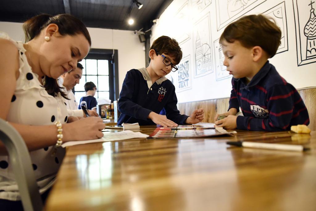 Juliana Rodríguez (izq.) junto a su hijo Nicolás Lamús y Sebastián del Potro, preparan sus estampas repetidas para intercambiarlas en el restaurante Arepa TX. BEN TORRES/Especial para Al Día