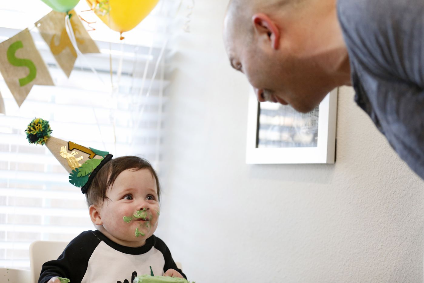 Hudson Marr looks at his father Chris Marr while eating cake during his one year birthday party at their home on Monday, March 15, 2021in Grapevine, Texas.