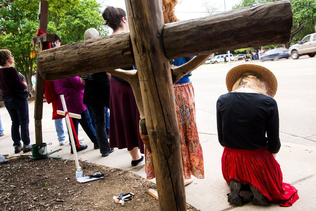 Abortion opponents kneel in prayer as they line Greenville Avenue during the Good Friday vigil outside the Southwestern Women's Surgery Center.