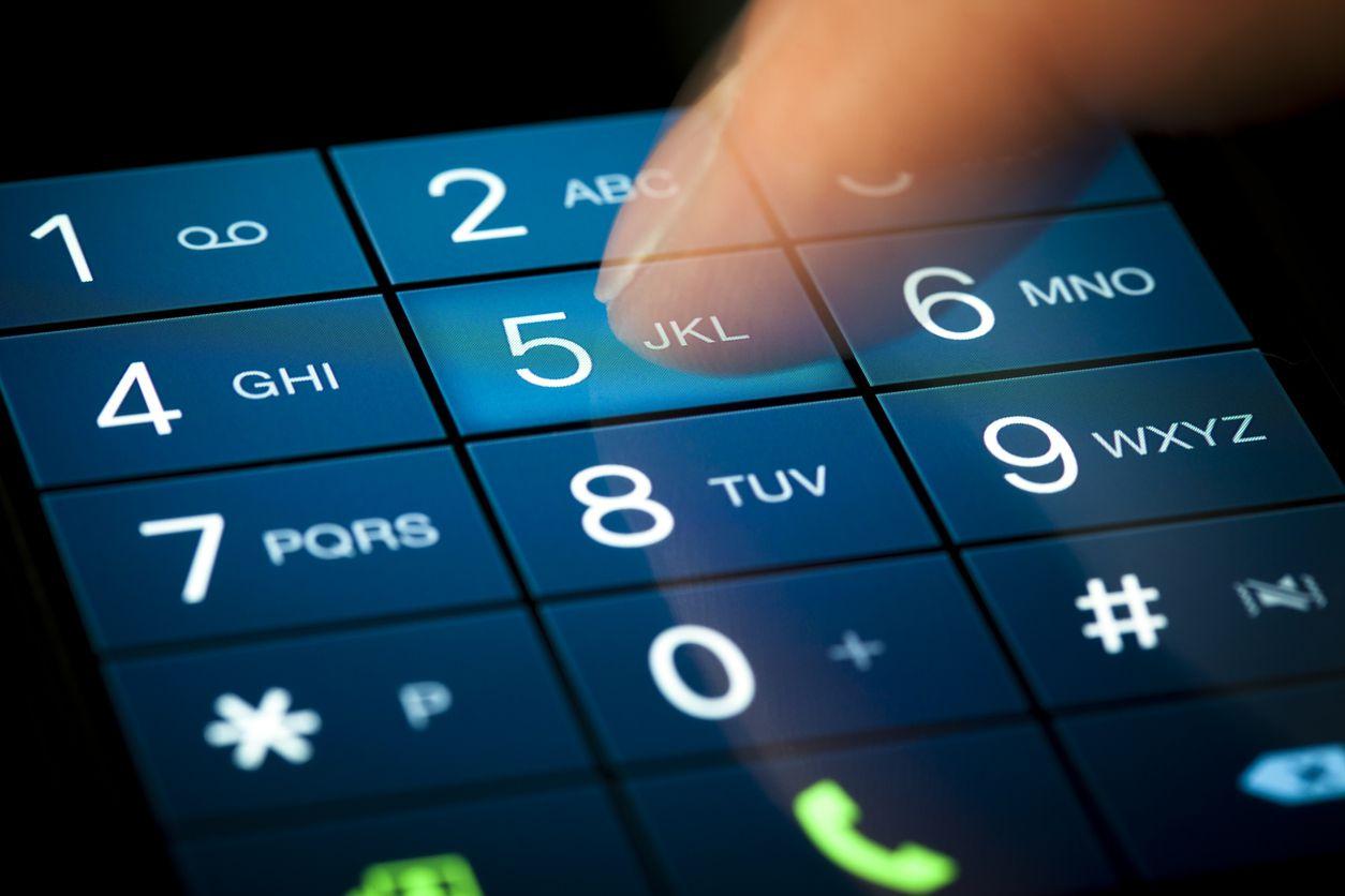 Una persona marca un número telefónico en un smartphone.