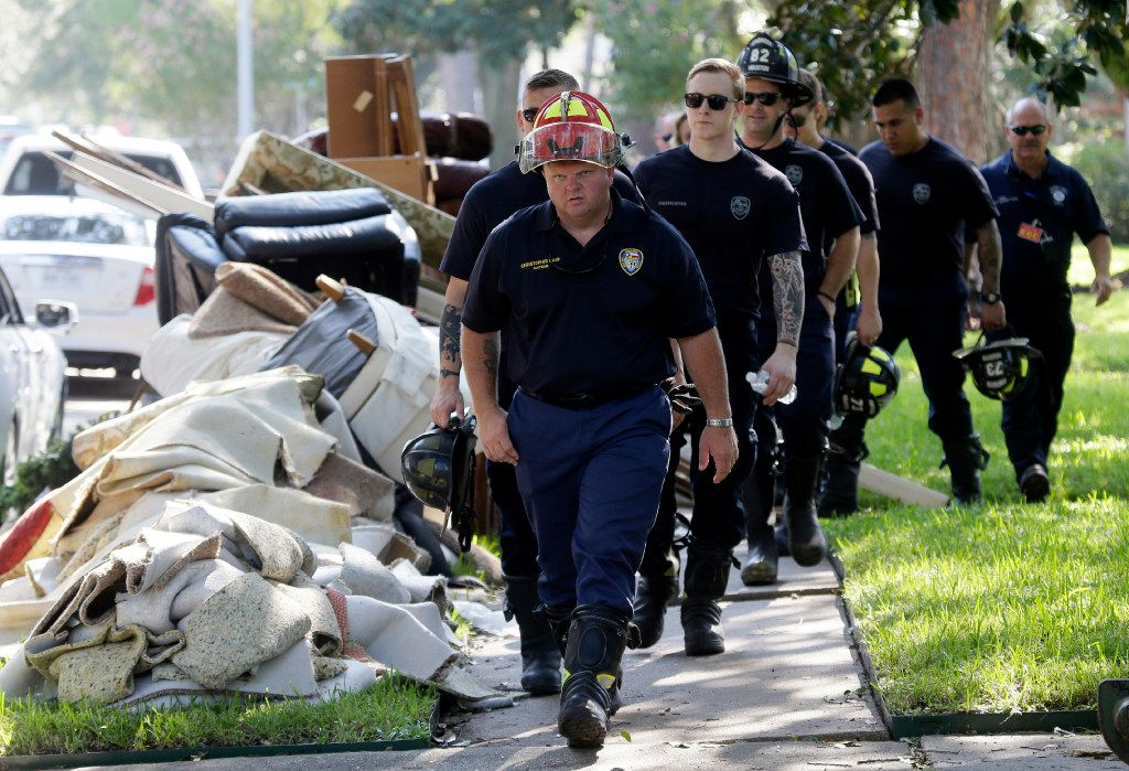 Firefighters walk around debris removed from homes during a door-to-door survey of a neighborhood that was swamped by floodwaters.