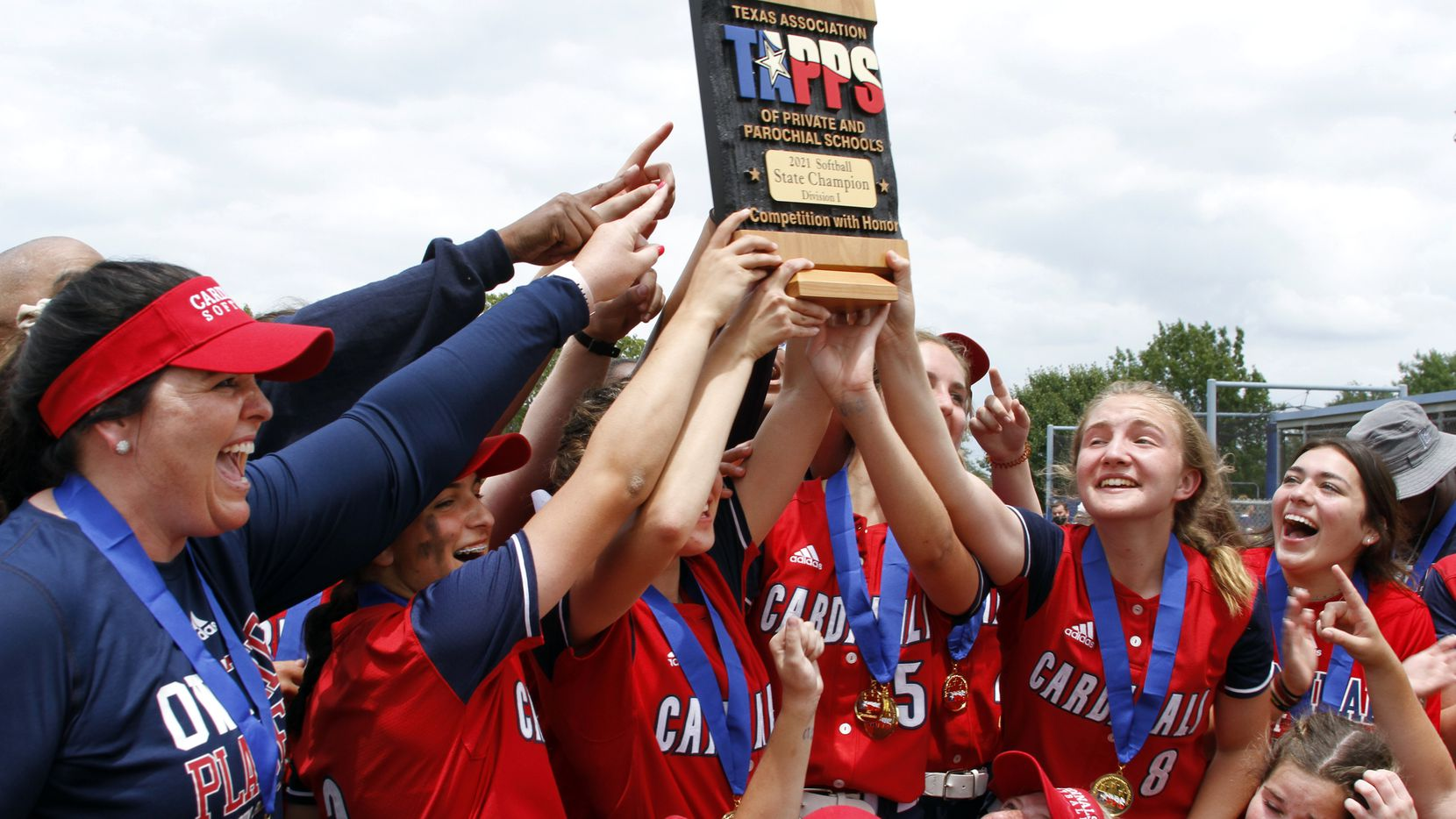 Plano John Paul ll softball coach Jayme Baker-Nelson (left) and her players celebrate by hoisting the state championship trophy following a 4-2 victory over San Antonio Antonian in the TAPPS Division I state title game Saturday at the Waco ISD Softball Complex. (Steve Hamm/Special Contributor)