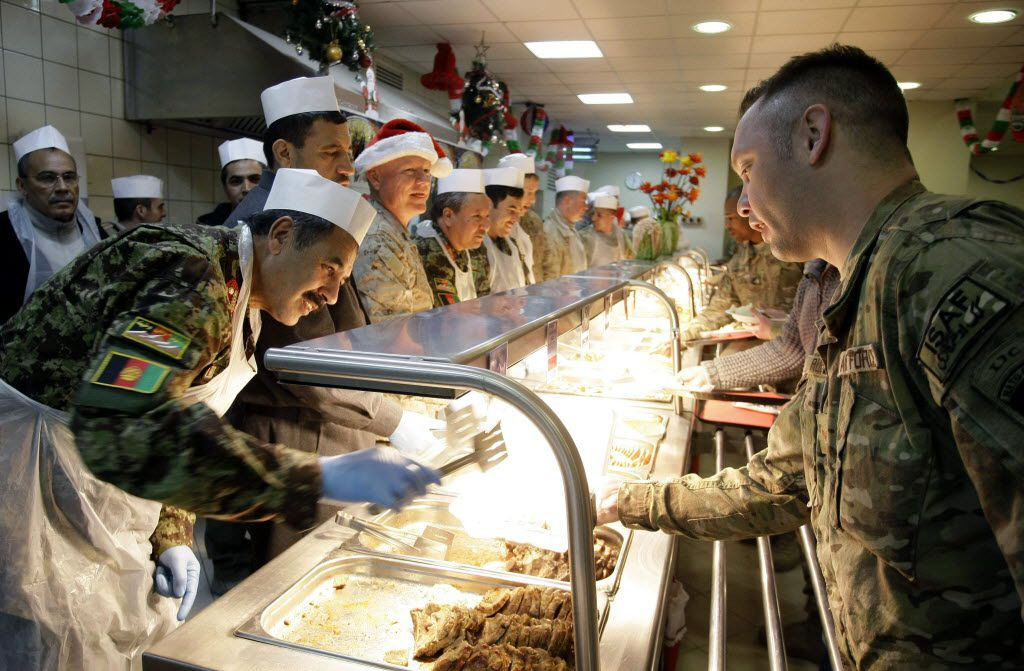 Afghan and U.S. generals, left, serve Christmas dinner to to U.S. soldiers and service members Soldiers and service members with the NATO-led International Security Assistance Force (ISAF) at a dining facility at the U.S.-led coalition base in Kabul, Afghanistan, Tuesday, Dec. 25, 2012. (AP Photo/Musadeq Sadeq)